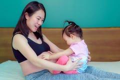 La piccola figlia che si siede madre asiatica di signora del rivestimento A della madre sulla bella è incinta fortunatamente immagini stock libere da diritti