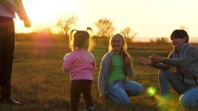 La piccola figlia gioca un calcio dei bambini con la sue madre e sorelle nel campo nei raggi di un bello video d archivio