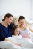 La piccola figlia legge ai genitori il libro Fotografia Stock