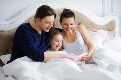 La piccola figlia legge ai genitori il libro Fotografie Stock Libere da Diritti