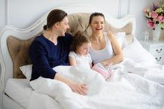 La piccola figlia legge ai genitori il libro Immagini Stock Libere da Diritti