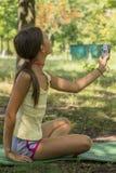 La piccola macchina fotografica sveglia della tenuta della ragazza a disposizione e prende un'immagine con selfie sparato in parc fotografia stock libera da diritti