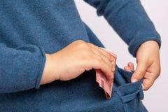 La piccola mano mette la banconota dell'euro dieci in tasca Fotografia Stock Libera da Diritti