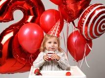 La piccola neonata celebra il suo secondo compleanno con il dolce dolce o fotografia stock libera da diritti