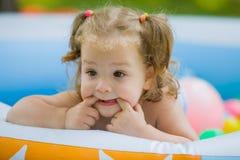 La piccola neonata che gioca con i giocattoli in stagno gonfiabile nel giorno soleggiato di estate Fotografia Stock
