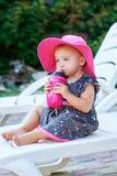 La piccola neonata nel parco di autunno beve dalla bottiglia di plastica rosa Immagine Stock Libera da Diritti