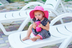 La piccola neonata nel parco di autunno beve dalla bottiglia di plastica rosa Immagini Stock