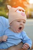 La piccola neonata sbadiglia in cappuccio divertente sulle mani del padre all'aperto alla luce solare di sera del fiore con i chi Fotografia Stock