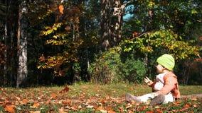 La piccola neonata si siede immobile su erba e gli sguardi alle foglie cadenti in parco il giorno in anticipo luminoso e soleggia stock footage