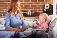 La piccola neonata si siede nel seggiolone e nell'alimentazione con il cucchiaio della sua bella madre Immagine Stock