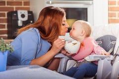 La piccola neonata si siede nel seggiolone e nell'alimentazione con il cucchiaio della sua bella madre Fotografie Stock