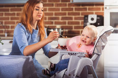 La piccola neonata si siede nel seggiolone e nell'alimentazione con il cucchiaio della sua bella madre Fotografia Stock