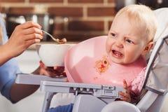 La piccola neonata si siede nel seggiolone e nell'alimentazione con il cucchiaio della sua bella madre Immagini Stock