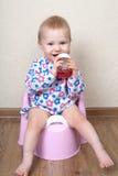 La piccola neonata, sta sedendosi su un vaso rosa e beve l'acqua Fotografie Stock