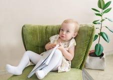 La piccola neonata sveglia fa il fronte divertente, giudicante il libro disponibile Bambino che si siede sulla poltrona Immagine Stock Libera da Diritti