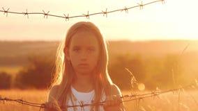 La piccola ragazza è al tramonto dietro filo spinato Il bambino passa la tenuta del cavo Il concetto di libertà e di immigrazione archivi video
