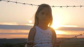 La piccola ragazza è al tramonto dietro filo spinato Il bambino passa la tenuta del cavo Il concetto di libertà e di immigrazione stock footage