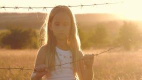 La piccola ragazza è al tramonto dietro filo spinato Il bambino passa la tenuta del cavo Il concetto di libertà e di immigrazione video d archivio