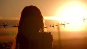 La piccola ragazza è al tramonto dietro filo spinato Il concetto di libertà e di immigrazione archivi video