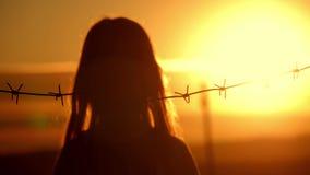 La piccola ragazza è al tramonto dietro filo spinato Il concetto di libertà e di immigrazione video d archivio