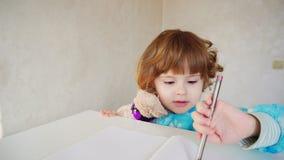 La piccola ragazza americana con la penna rosa impara disegnare Fotografie Stock