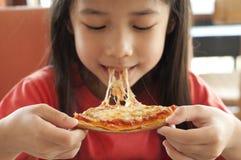 La piccola ragazza asiatica gode della pizza. Fotografia Stock Libera da Diritti