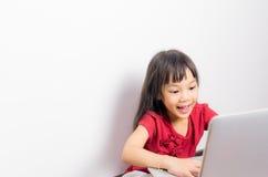La piccola ragazza asiatica sta avendo pistola che pratica il surfing Internet immagine stock