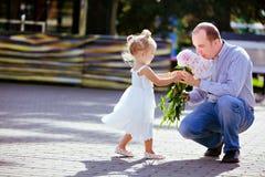 La piccola ragazza bionda adorabile dà le peonie di papà Immagini Stock