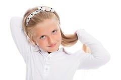 La piccola ragazza bionda pone i suoi capelli lunghi Immagine Stock