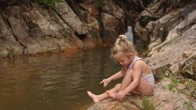 La piccola ragazza bionda si siede pulisce il piede sulla pietra dalla cascata video d archivio