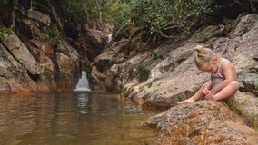 La piccola ragazza bionda si siede pulisce il piede sulla pietra dalla cascata stock footage
