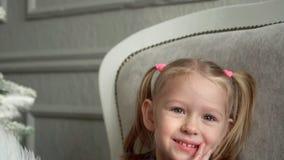 La piccola ragazza bionda sorridente gioca su un sofà ad un abete La piccola ragazza bionda sorride sedendosi su un sofà stock footage