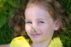 La piccola ragazza bionda sta trovandosi sulla terra e sta esaminando la macchina fotografica con il gambo dell'erba verde nella  fotografia stock