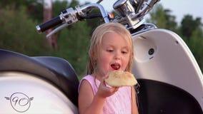 La piccola ragazza bionda sulla spiaggia La bambina mangia il rotolo durante il declino al mare Il piccolo bambino al video d archivio