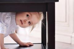 La piccola ragazza bionda sveglia in camicia a strisce ha scalato in tavola di cavità Immagini Stock Libere da Diritti