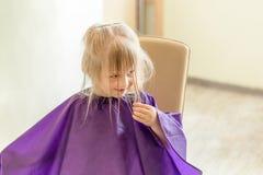 La piccola ragazza bionda sveglia sorride ed esamina il parrucchiere durante il processo di taglio di capelli La ragazza tiene i  fotografie stock