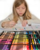 La piccola ragazza bionda sveglia sta disegnando dalle matite variopinte, scatola di matite sulla priorità alta Fotografia Stock
