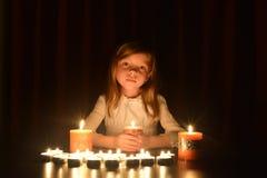 La piccola ragazza bionda sveglia tiene una candela bruciante I lotti delle candele sono intorno lei, sopra fondo scuro immagini stock