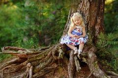 La piccola ragazza bionda in vestito e cappello luminosi si siede in un'abetaia Immagini Stock Libere da Diritti