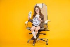 La piccola ragazza castana con gli orologi e incassa la sedia Fotografia Stock