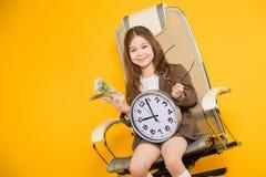 La piccola ragazza castana con gli orologi e incassa la sedia Immagine Stock