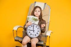 La piccola ragazza castana con gli orologi e incassa la sedia Fotografie Stock