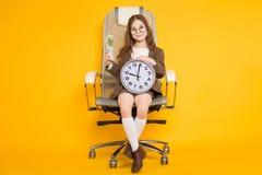 La piccola ragazza castana con gli orologi e incassa la sedia Immagini Stock