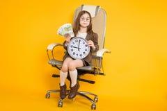 La piccola ragazza castana con gli orologi e incassa la sedia Fotografie Stock Libere da Diritti