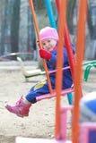 La piccola ragazza del bambino in camice caldo blu scuro sta sedendosi sull'oscillazione dei campi da giuoco Fotografia Stock