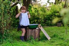 La piccola ragazza dell'assistente lava i vestiti in un bacino all'aperto Fotografia Stock