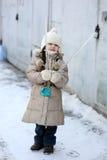 La piccola ragazza di inverno con capelli lunghi tiene il grande ghiacciolo Immagini Stock