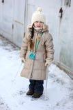 La piccola ragazza di inverno con capelli lunghi tiene il grande ghiacciolo Immagini Stock Libere da Diritti