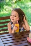 La piccola ragazza felice beve il succo d'arancia da un vetro in un caffè su un fondo erboso Fotografie Stock Libere da Diritti