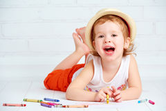 La piccola ragazza felice dell'artista in un cappello estrae la matita immagini stock